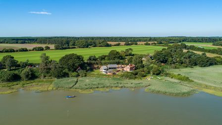 Sweeping vista with river in the foreground, Jumbos Cottage in the centre and large swathes of grassland and fields behind