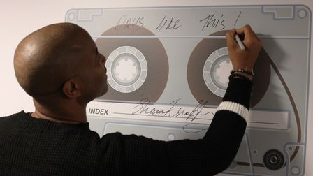 Shaun Escoffery signs the wall of the newly named Shaun Escoffery Studio at the East London Institute of Technology