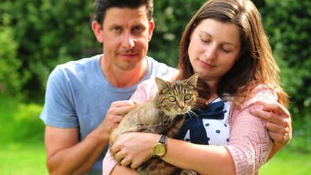 Scout the cat recovering at home with owners Jennifer Heath and James Jermy after having her leg amp