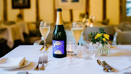 Wyken Vineyards' award-winning Moonshine sparkling wine on a table with cutlery and linen