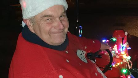 A man wearing a Santa hat and Christmas jumper smiles for the camera.