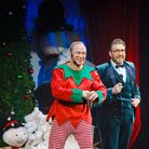 To the left, comedian Ben Langley wears an elf costume while to the right Hippodrome Circus host Jack Jay wears a teal...