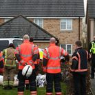 Members of the Cambridgeshire Fire and Rescue Service lay flowers at the scene of a house fire on Buttercup Avenue...