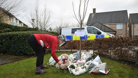 A woman places a teddy bear with other tributes at the scene of a house fire on Buttercup Avenue, Eynesbury...