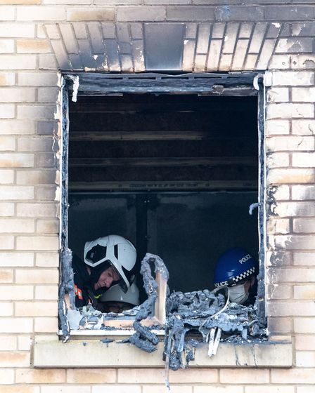 Fire investigators in the burnt out window of a house fire on Buttercup Avenue, Eynesbury, Cambridgeshire, where a...