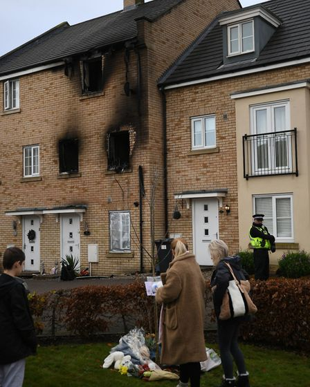 People lay flowers at the scene of a house fire on Buttercup Avenue, Eynesbury, Cambridgeshire, in which a three-year-old...