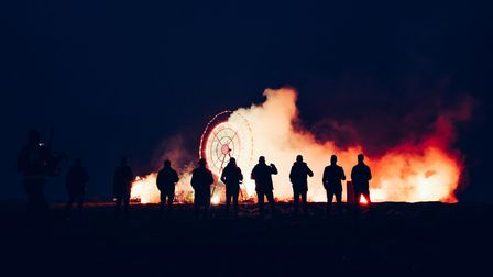 A 18 foot metal wheel on a beach with fireworks