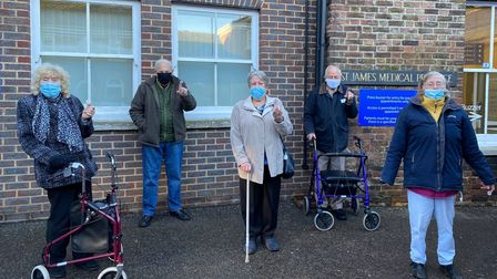 Elderly people stand outside a GP in Kings Lynn holding up their vaccine sticker.