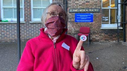 Elderly woman holding her vaccine sticker outside the GP