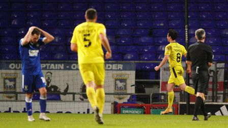 Alan Judge has his hands on his head as Joe Powell wheels away after levelling for Burton Albion.