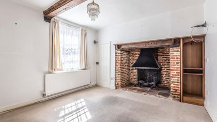 Bright white sitting room with a window timber beam and brick fireplace