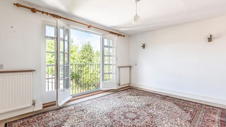 White bedroom with traditional wooden doors and big windows opening out on to a balcony with trees in the distance