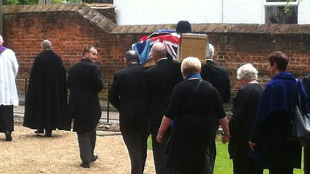 William Lister's coffin, draped in the RAF flag with a police helmet on top is carried into St John'