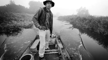 Eel catcher Peter Carter going out on the Well Creake to trap eels on a misty dawn out on the fens.