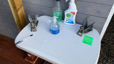 A white table with cleaning products on it.
