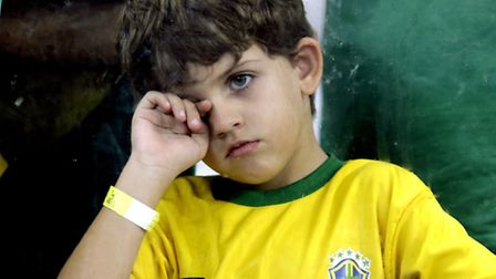A young supporter watches on as Germany defeat Brazil 7-1 to advance to the World Cup final.