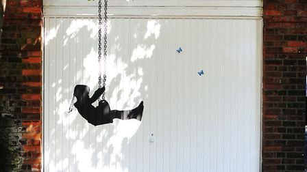 An image of a little girl on a swing which has been painted onto a garage in Great Yarmouth by the a