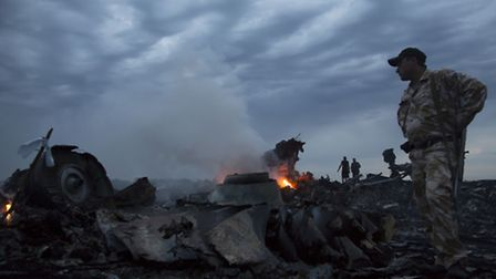 People walk ammong debris from Flight MH17. Picture: PA.