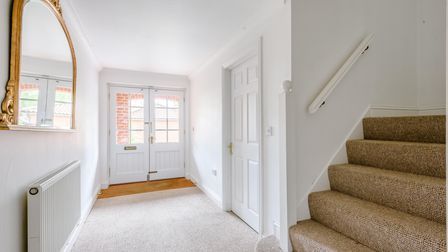 Large white entrance hall with a white door and carpeted stairs in the foreground