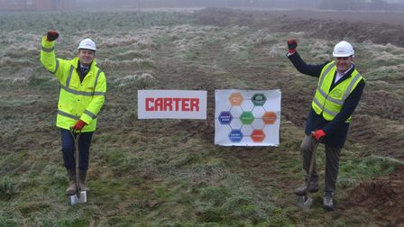 Two men wearing high viz plant spades into the ground