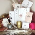 Scented candles, diffusers and gift bags on a table