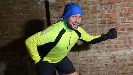 Tom Knight in his running gear in front of a brick wall