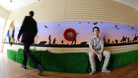 The commemorative community mural, with artist and photographer Lewis Bond. Picture: Matthew Usher.