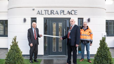 Three men at ribbon cutting ceremony for new properties