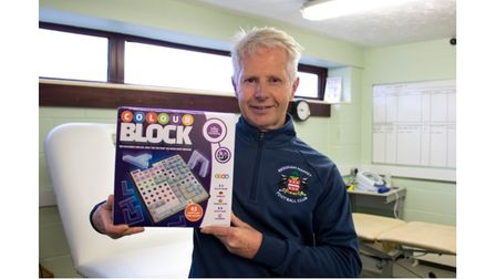 Ian Jenkins holding his newly released board game, Colour Block to the right of his head