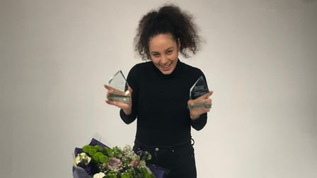 Joelle Mae David holding her two Women's Empowerment Awards behind a bouquet of flowers