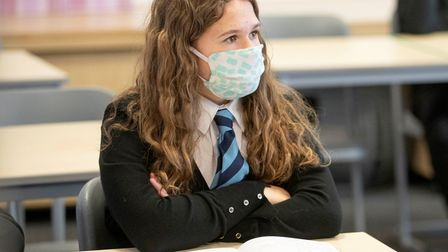 A secondary school student wears mask but most will be learning from home on their return in January.