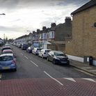 Cars parked along Holmwood Road, Ilford, from the intersection with Green Lane.