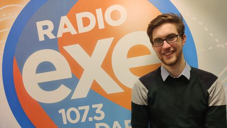Jamie Taylor stood in front of a large Radio Exe poster