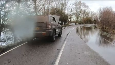 Photographer Terry Harris drives throughthe flooded A1101 atWelney.