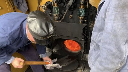 Volunteer fireman Jamkes Quinlan shovels coal into the firebox of the Class Y14 locomotive on the No