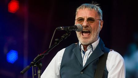 Rock star Steve Harley singing into a microphone and playing guitar