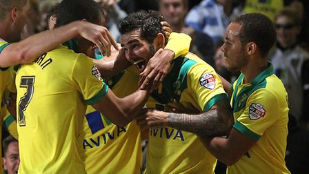 Bradley Johnson is swamped by his Norwich City team mates after another stunning solo effort in the