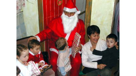 Father Christmas handing out gifts at a baby unitsupport group's party in Bury St Edmunds in 2003