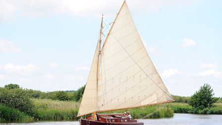 A boat from the hunters fleet sailing on the River Bure near St Benets Abbey on the Norfolk Broads.
