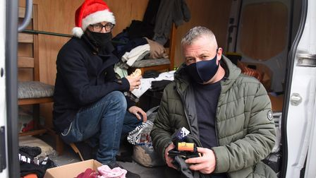 John Warrilow, left, and Denzil Flack from Thetford, giving away clothes at the Norwich Open Christm