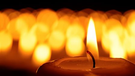 Candle in front of many defocused candleflames creating a spiritual atmosphere and in remembrance of