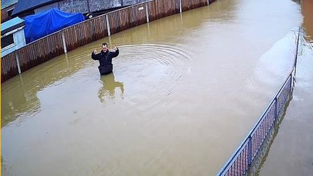 Beccles Lido site manager Carl Murray wades in the flood waters to access the attraction and prevent further damage.