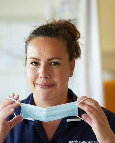 Michelle Wigger, a nurse at the Norfolk and Norwich University Hospital, holds a face mask.