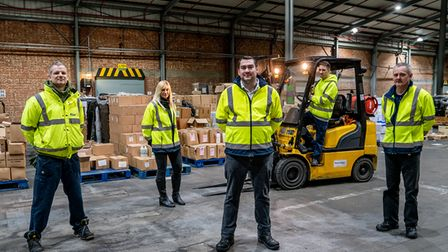 Five members of the Norse distribution team stand in their warehouse, with a forklift truck and boxes in the background.