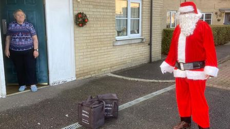 Father Christmas is pictured delivering one of the Christmas dinners.