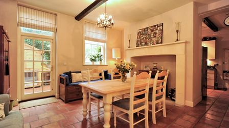 Country kitchen style table chairs on terracotta floor tiling
