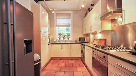 Cream coloured kitchen with base and wall units and a window overlooking the garden