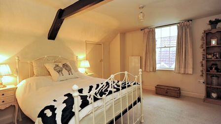 Double bed in large bedroom with exposed beam across the ceiling