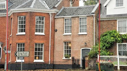 Two attached townhouses with sash windows on main ring road into Norwich city centre
