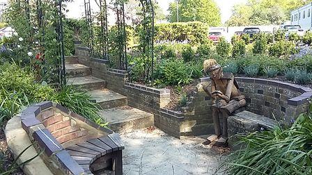small garden with paving, seats, sculpture, plants